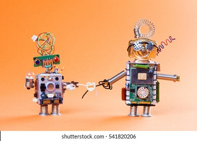 Robot love story concept. Funny circuit socket toys with lamp bulb and love heart symbol. Cute faces, blue red eyes and glasses. light gradient orange color background.