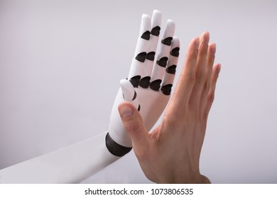 Robot And Man Giving High Five On Grey Background