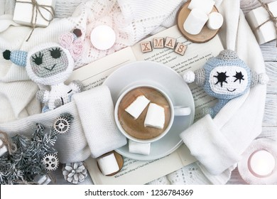 Robot and robotics. A cup of coffee with marshmallows stands on the open book. A warm sweater. New Year's and Christmas. Christmas tree and gifts of jewelry, bracelets with charms. Huggy concept.