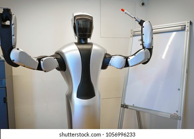 Robot teacher standing in front of board. Milan, Italy - February 2017