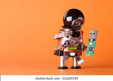 Robot with usb flash storage stick. Data storing and robotic technology concept, fun toy character black helmet head. Copy space, orange background, macro view soft focus.