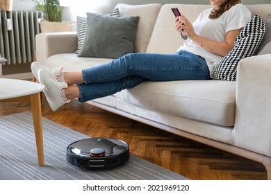 Robot vacuum cleaner cleaning the living room. Young woman enjoy rest, sitting on sofa at home - Shutterstock ID 2021969120