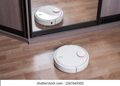 Robot vacuum cleaner on laminate floor is reflected in mirror of wardrobe, smart home robotics wireless cleaning for simplify routine housework, efficient dust absorption in absence of householder.
