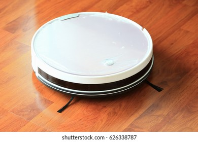Robot vacuum cleaner on laminate wood floor, Smart robotic automate wireless cleaning technology machine in bedroom.