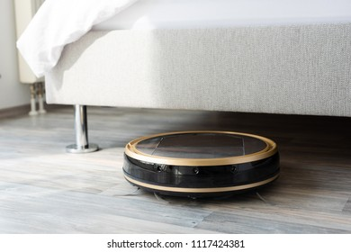 Robot vacuum cleaner runs under bed in bedroom, modern and convenient smart cleaning technology