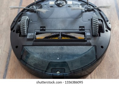 Robot vacuum cleaner upside down on the floor. Covered with dust after cleaning.