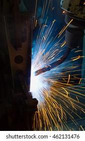 Robot welding automotive part in factory.