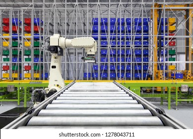 Robotic arm loading plastic crates on pallet. on rollers steel for transport belt conveyor turning of manufacture. automate processes production on factory, logistics technology of industry concept.