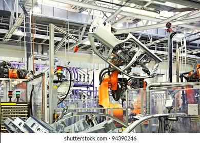 robotic arms in a car factory