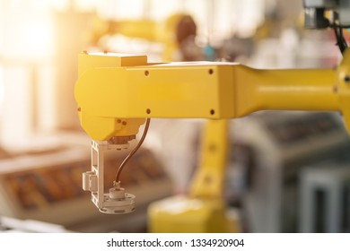 robotic assembly arm in modern factory with sunflare from window