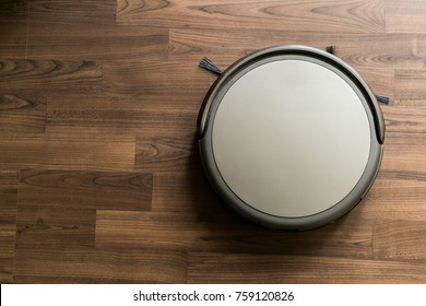 Robotic drone vacuum cleaner on laminate wood floor smart cleaning technology.