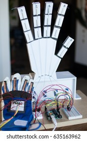 Robotic hand controlled by servomotors and glove with bending sensors. Robotic education for students and children, coding and making for classroom technologies activities