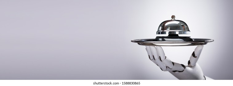 Robotic Hand Holding Bell On Silver Plate Against Grey Background