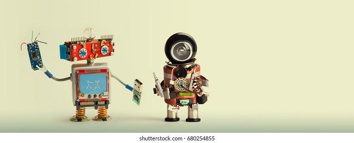 Robotic maintenance repair fix concept. Handyman robots, smiley red head, chip usb flash stick. Mechanic cyborg toy with black helmet, electronic accessories, screwdriver. Copy space, beige background