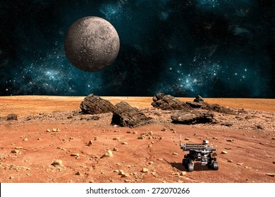 A robotic rover explores the surface of a rocky and barren alien world. A large cratered moon rises over the airless environment.  - Elements of this image furnished by NASA.