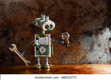 Robotic toy character lamp in hand, rusty iron surface. Vintage textured wall backdrop. Shallow depth field.