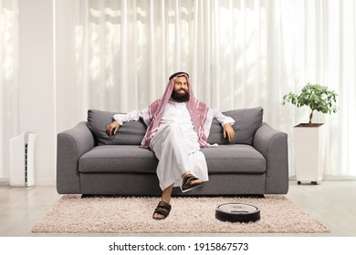 Robotic vacuum cleaner cleaning a carpet and a saudi arab man resting on a sofa at home