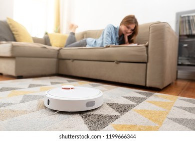 Robotic vacuum cleaner cleaning the room while woman relaxing on sofa. Woman controlling vacuum with remote control.