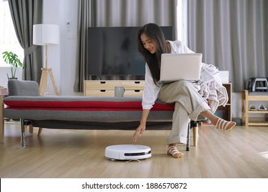 Robotic vacuum cleaner cleaning the room while woman working with laptop computer on sofa at home.