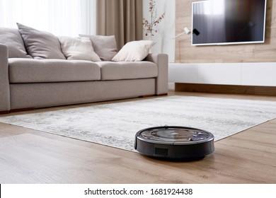 Robotic vacuum cleaner on the floor in cozy modern living room