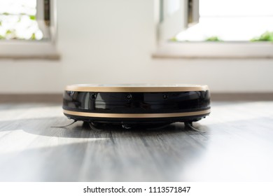 robotic vacuum cleaner on laminate wood floor with bright windows in the background, modern and convenient smart cleaning technology