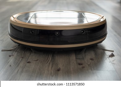 robotic vacuum cleaner on laminate wood floor with dust around, modern and hygienic smart cleaning technology. Focus on hairs and dust.