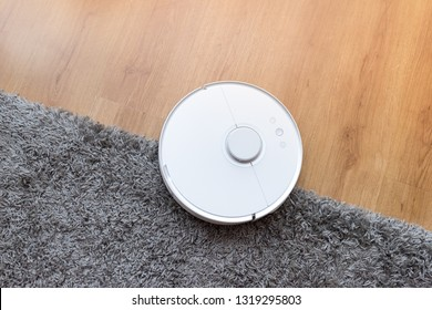 Robotic vacuum cleaner on laminate wood floor and gray carpet. Smart cleaning technology