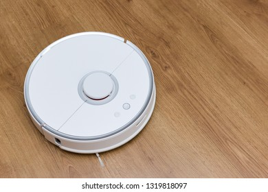 Robotic vacuum cleaner on laminate wood floor. Smart cleaning technology