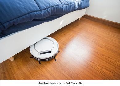 Robotic vacuum cleaner on laminate wood floor in bedroom.