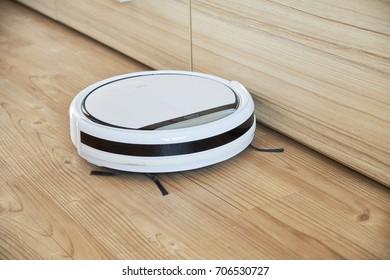Robotic vacuum cleaner on wooden floor.
