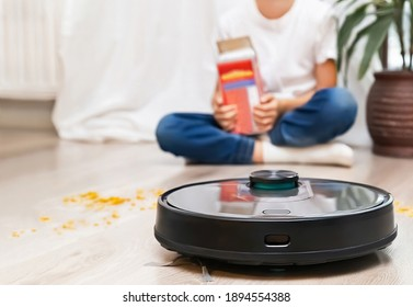 Robotic vacuum cleaner ready to easily remove the flakes, which were scattered by child during eating. Focus is on the robotic vacuum cleaner with blurred background. Smart home, housework concept.