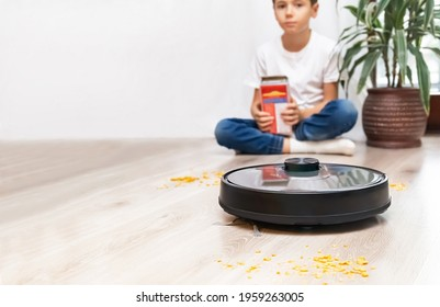 Robotic vacuum cleaner ready to easily remove the flakes, which were scattered by child. Focus is on the robotic vacuum cleaner with blurred background. Smart home, housework concept. Copy space.