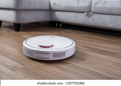 Robotic vacuum cleaner runs near sofa in room on laminate floor. Robot controlled by voice commands to direct cleaning. Modern smart cleaning technology housekeeping.
