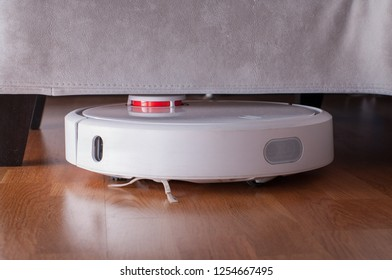 Robotic vacuum cleaner runs under sofa in room on laminate floor. Robot controlled by voice commands to direct cleaning. Modern smart cleaning technology housekeeping.