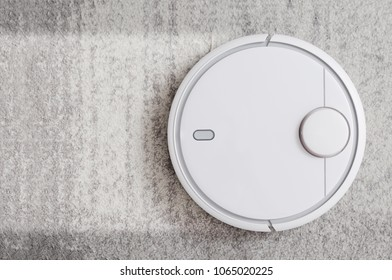 Robotic vacuum cleaner working on carpet top view concept