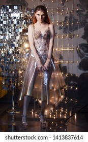 robotic woman in a plastic dress, future fashion concept. Stylish young woman in transparent latex dress