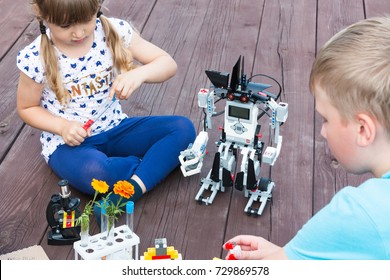Robotics class in school or camp. The teacher explains the lesson to the girl and teenager boy. Lego robot, Mindstorms, EV 3, tubes, microscope. Stem education. Minsk, Belarus - August, 2017.