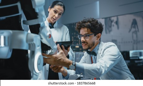 In Robotics Development Laboratory: Chief Female Engineer and Top Male Scientist Work on a Bionics Exoskeleton Prototype. Designing Powered Exosuit to Help Disabled People, Hard Labor Workers