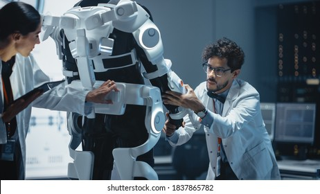 In Robotics Development Laboratory: Chief Female Engineer and Top Male Scientist Work on a Bionics Exoskeleton Prototype. Designing Powered Exosuit to Help Disabled People Walk, Workers Lift Goods