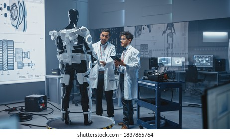 In Robotics Development Laboratory International Team of Engineers and Scientists Work on Robotics Exoskeleton Prototype. Designing Powered Exosuit to Help Disabled People Walk, Workers to Lift Goods