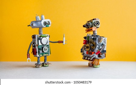 Robots on yellow background. 4th industrial revolution automation concept. Robotic serviceman with screwdriver, creative design cyborg toys. Maintenance repair fix concept