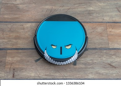 Robots takeover, robots as pets and evil robots concepts. Robot vacuum cleaner on the floor with eyes and evil smile.