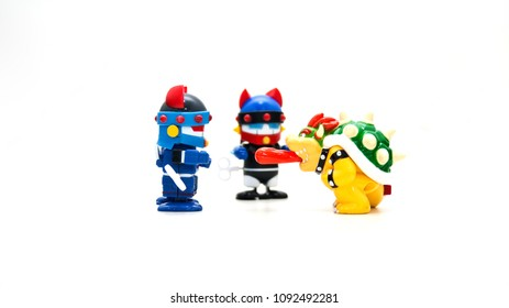 Robots wearing two blue helmets on a white background are paying attention to the monsters that have their red tongue out.