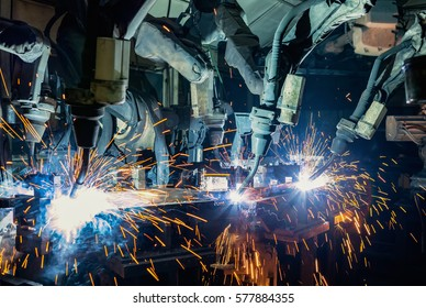 Robots are welding automotive part in car factory.