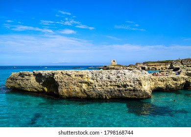 Roca Vecchia, Italy - August 18th 2016: Photo of a beautiful blue, almost deserted bay with turquoise, clear water, surrounded by stone cliffs and an old ruin in the background on a hot summer day