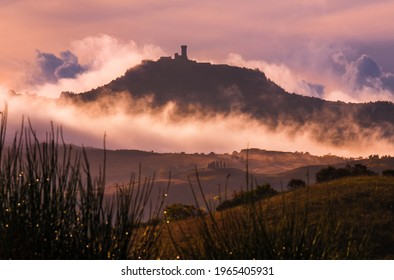 Rocca di Radicofani main tower fortification covered with morning mist. Sunrise light covering the curly clouds running over meadows and fields making light-shadows playing on Tuscany hills landscape.