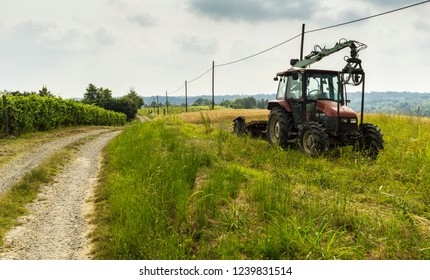 Rocchetta Tanaro, Piedmont, Italy - July 2, 2018: Dirt road and tractor among wheat fields in Piedmont (North Western Italy), in July.