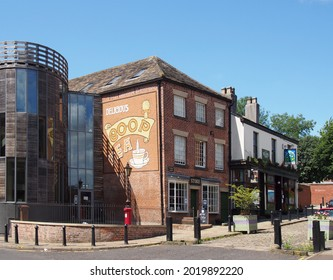rochdale, greater manchester, united kingdom - 14 July 2021: view of the rochdale pioneers co-operative store in toad lane now a museum with old  tea advertisement on the wall