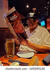 ROCHELLE PARK, NEW JERSEY - AUGUST 17, 2019: A diner at a local Outback Steakhouse holding a menu while trying to decide what to eat. Outback Steakhouse is an American casual dining restaurant chain.