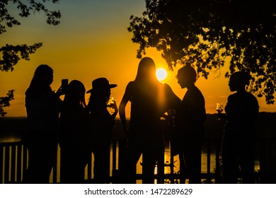 Rocheport, Missouri, USA -- July 23, 2019: Silhouettes of young women enjoying beautiful sunset and drinking wine on deck above Missouri River  in summer in Missouri